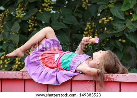 European smiling young girl eating ice cream berry lying on a bench in a summer park/Cute child lying on a bench and eating ice cream outdoors - stock photo