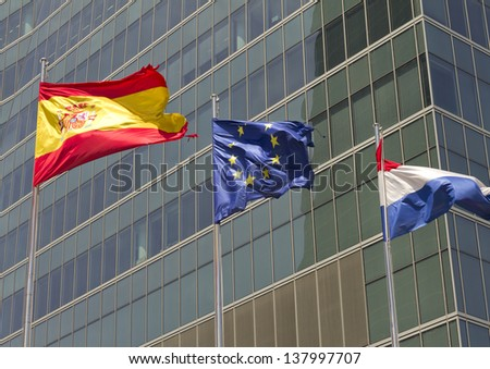 European, spanish and french flag with modern building on the background - stock photo