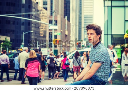 European student in New York. Wearing blue pattered short sleeve shirt, jeans, young guy sitting on street surrounded with tall buildings, relaxing. Many people walking on background. Instagram effect - stock photo