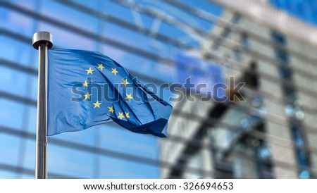 European Union flag in front of the Berlaymont building (European commission) in Brussels, Belgium. - stock photo