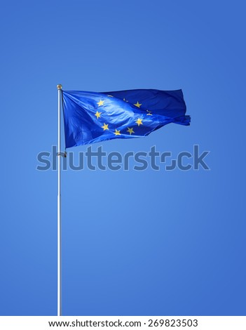 European Union flag on flagstaff waving against blue sky. Clipping path is included - stock photo