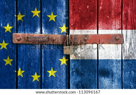 European Union flag with the Holland flag on the background of old locked doors - stock photo