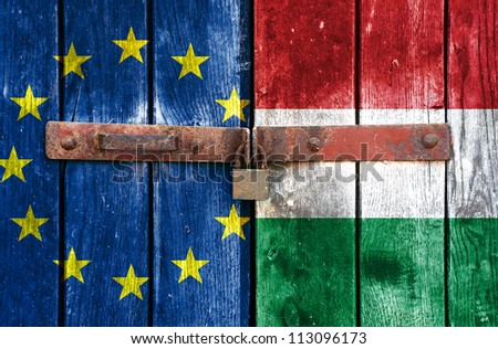 European Union flag with the Hungary flag on the background of old locked doors - stock photo