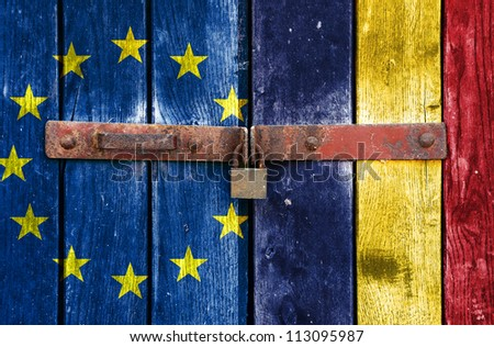 European Union flag with the Romanian flag on the background of old locked doors - stock photo