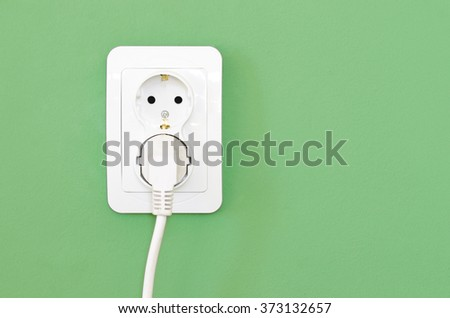 European white electrical outlet socket and white cable plugged in isolated on green wall - stock photo