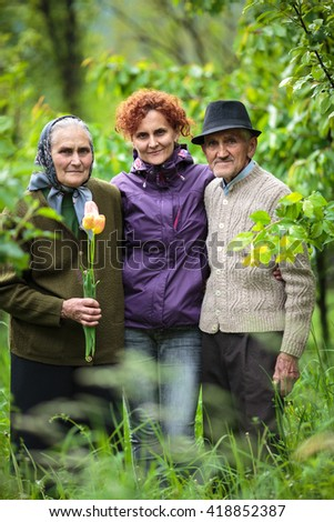 European woman and her old parents in the garden - stock photo
