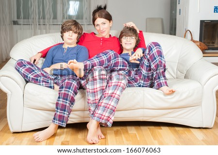 European woman with two sons in their pajamas on the couch - stock photo