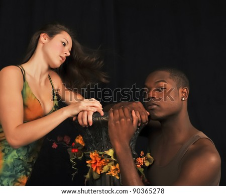 Eve tempting Adam on a black background in the garden of eden. - stock photo