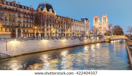 Eveing panorama of Paris with illuminated  Notre-Dame cathedral - stock photo