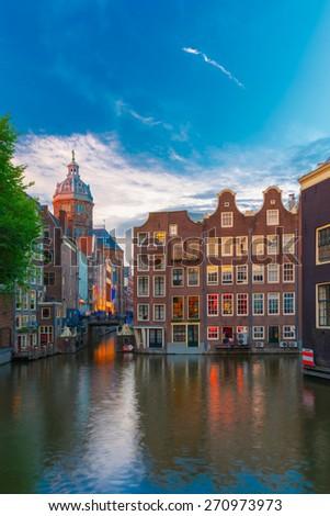 Evening Amsterdam canal, church and bridge - stock photo