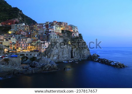 Evening at a Village by the Sea. A dusk photo of the Italian village of Manarola, located in the Cinque Terre National Park region. The village harbor lies beneath. - stock photo