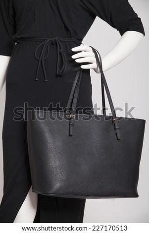 Evening black dress and handbag on a dummy isolated on white. Vertical , studio shot.  - stock photo