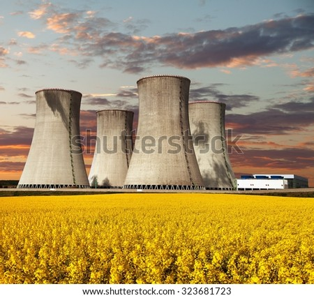 Evening colored view of nuclear power plant Dukovany with golden glowering field of rapeseed - Czech Republic - two possibility for production of energy  - stock photo