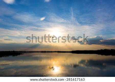 Evening landscape with nice sunset on lake - stock photo