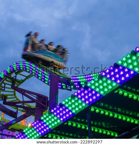 Evening lights and colors of carousel in amusement park - stock photo