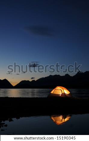 Evening lit tent in camping by nature - stock photo