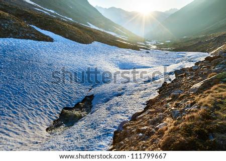 Evening mountain stream and sunset (near Timmelsjoch - high alpine road on Italian - Austria border) - stock photo