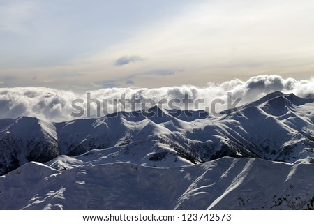 Evening mountains in clouds. Caucasus Mountains, Georgia, view from ski resort Gudauri. - stock photo
