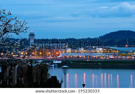Evening Portland airport with lights reflecting in the water of the Columbia River, spring flowering tree in the foreground and hills covered with trees against the dark blue sky - stock photo