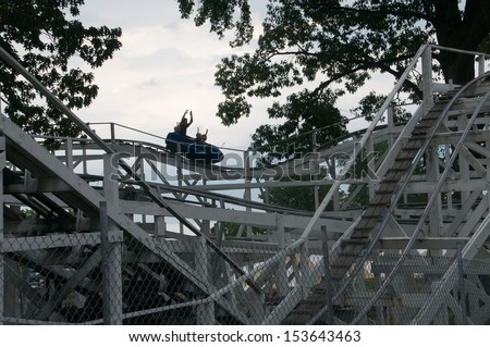 Evening ride on the roller coaster with a family enjoying the ride - stock photo