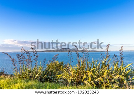 Evening sea view with a volcanic island on a horizon. Rangitoto island in Hauraki Gulf, Auckland, New Zealand - stock photo