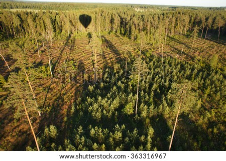 Evening shadow of air balloon on green landscape - stock photo