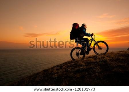 evening silhouette of a man climbing a mountain tourist on a bike - stock photo