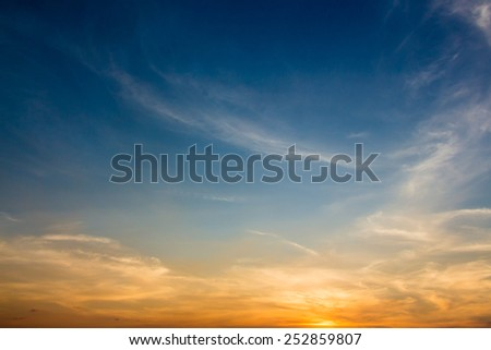 Evening sky scene with golden light from the setting sun and blue sky filled with white cloud streaks - stock photo