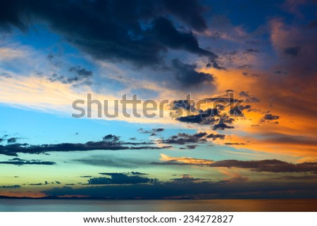 Evening sky with colorfully lit clouds shortly after sunset over Lake Titicaca viewed from the small tourist town of Copacabana in Bolivia  - stock photo