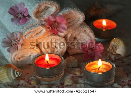 Evening Spa composition - towels, aromatic flowers and candles, shells on white sand - stock photo