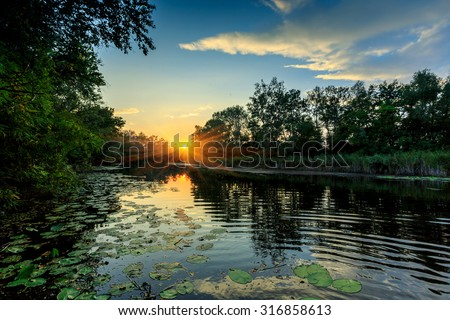 Evening sunset scene on river - stock photo