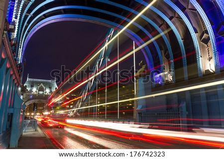 evening traffic lights and routemaster bus on the london tower bridge - stock photo