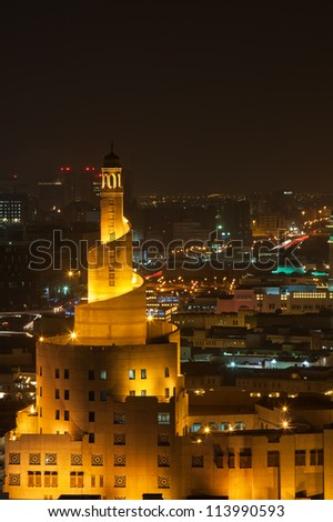 evening view of a mosque, lit up in yellow light against a dark dusty sky - stock photo