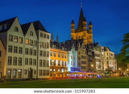 Evening. View of historic houses on the Rhine promenade in Cologne with Great St. Martin Church, Germany - stock photo