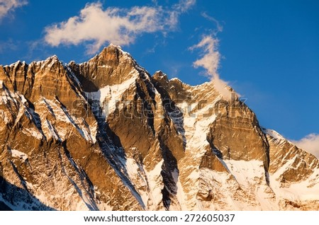 evening view of Lhotse and clouds on the top warm tone - Way to Everest base camp, three passes trek, Everest area, Sagarmatha national park, Khumbu valley, Nepal - stock photo