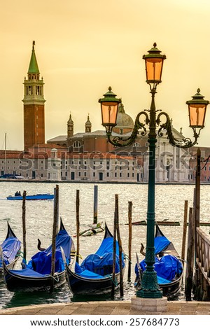 Evening view to San Giorgio Maggiore venice, Italy. Lamppost and gondolas on foreground.