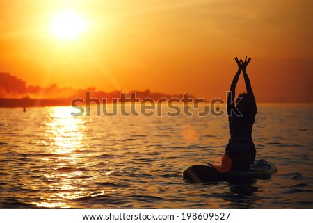 Evening yoga meditation on the paddle surf board at amazing bright sunset reflected on the ocean, silhouette of the girl engage yoga - stock photo
