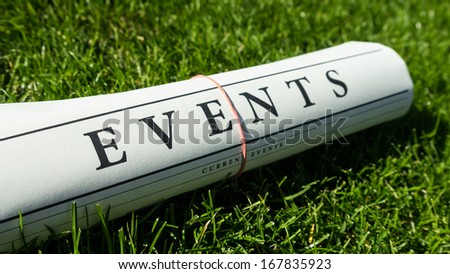events newspaper on a green meadow - stock photo