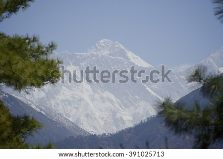 Everest through trees. Namchebazar or Namche view - stock photo