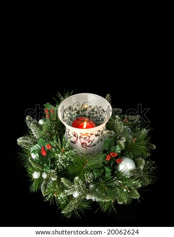 Evergreen centerpiece candle with greenery, isolated on black, lots of room for copy - stock photo