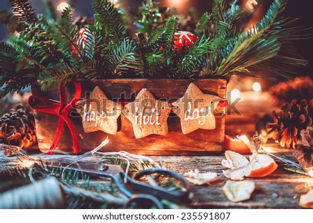 Evergreen Christmas centerpiece with Happy holidays gingerbread cookies and lights  - stock photo