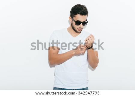 Every detail is important. Handsome young Indian man adjusting his bracelet and looking at camera while standing against white background - stock photo