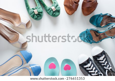 Every girl needs. Overhead of essentials for modern young woman. Different ladies shoes on white wooden background. - stock photo