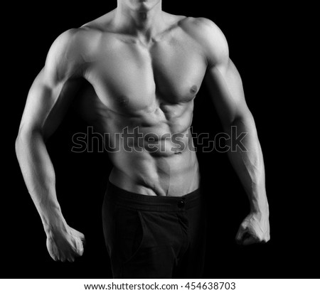 Every inch is perfect. Cropped monochrome shot of a fit and toned man posing shirtless - stock photo