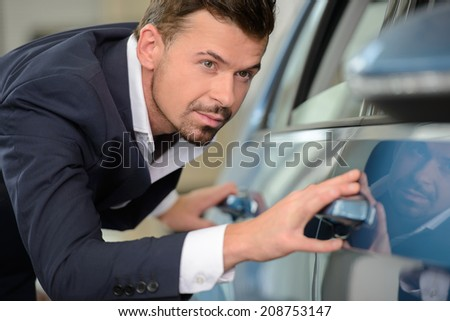 Every line should be perfect. Confident businessman examining a car at the dealership - stock photo