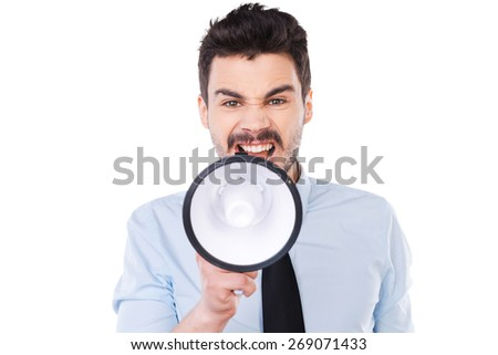 Everybody listen to me! Furious young man in shirt and tie holding megaphone and shouting while standing against white background - stock photo