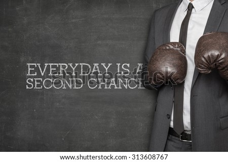 Everyday is a second change on blackboard with businessman wearing boxing gloves - stock photo