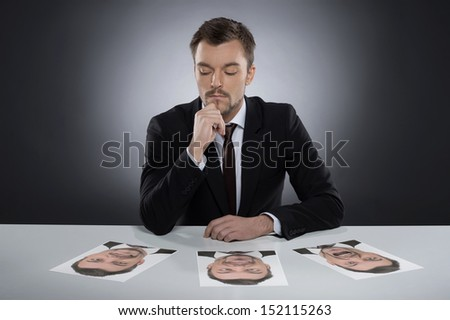 Everyday masks. Thoughtful young man sitting at the table and choosing the photographs of himself lying on it while isolated on grey - stock photo