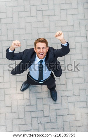 Everyday winner. Top view of happy young man in formalwear keeping arms raised and expressing positivity while standing outdoors - stock photo