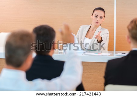Everyone is welcome for discussion. Confident young woman in formalwear giving a word to someone from audience while sitting in conference hall  - stock photo